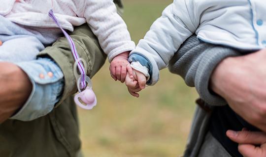 2 bébés le tiennent la main